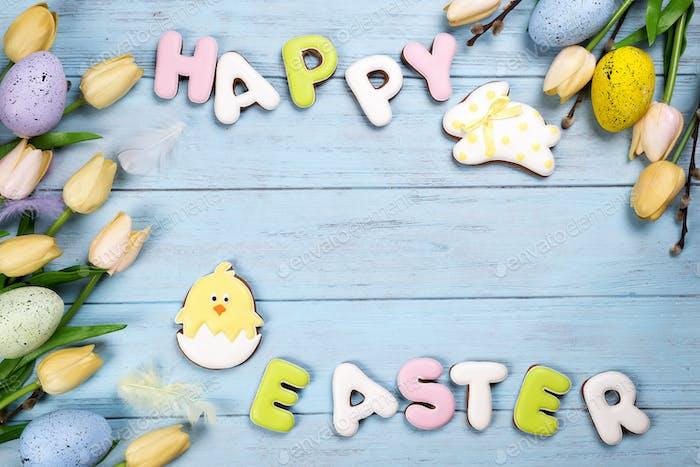 Frohe Ostern bunte Schriftzug Frohe Ostern von Ingwer Kekse und Kekse Hase auf Holz blau