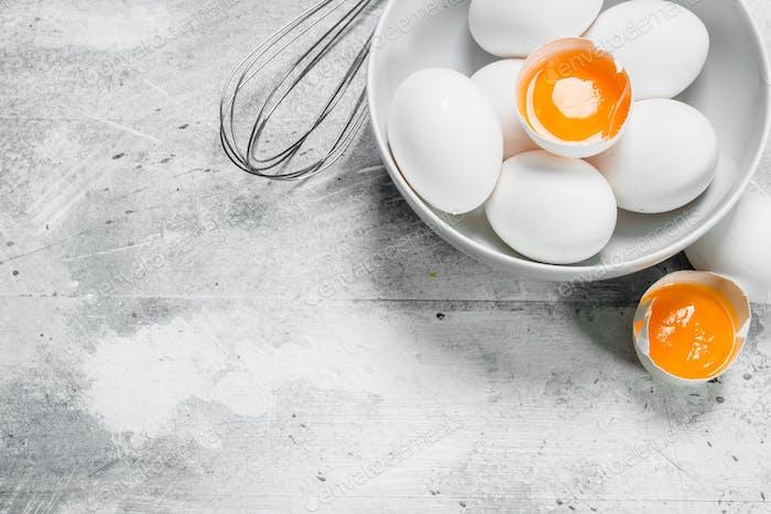 Eier in Schüssel mit Schneebesen.