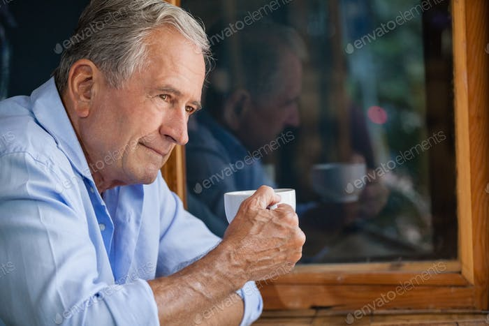 Man holding coffee cup while sitting in cafe shop