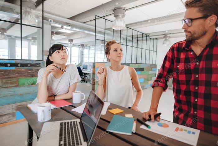 Startup Treffen um einen Tisch im modernen Büro