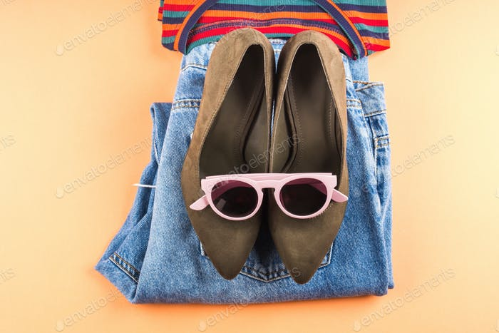 Fashion flat lay with jeans and glasses on orange