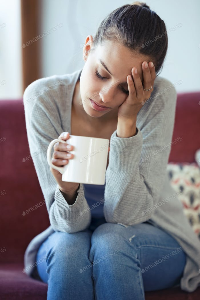 Depressed young woman having headache while drinking coffee on sofa at home.