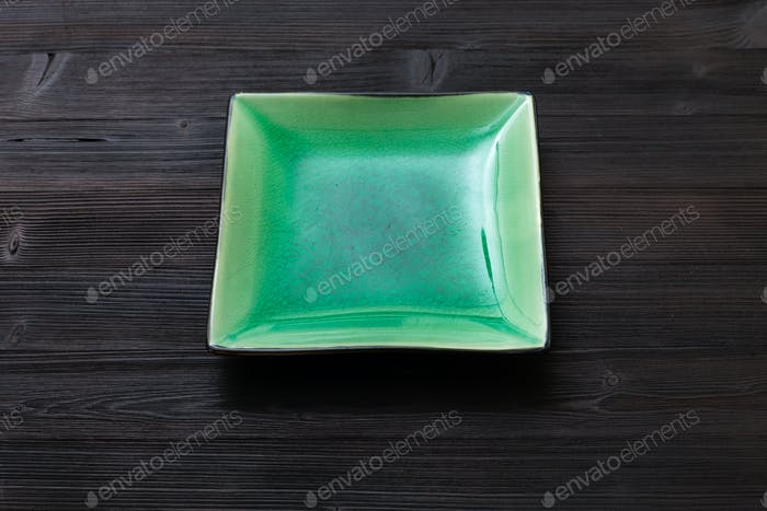 green square saucer on dark brown table