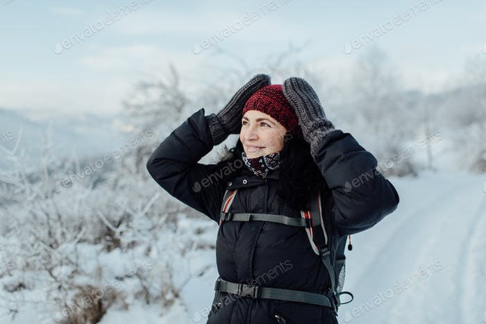 Smiling woman dressed warm admiring snowy country