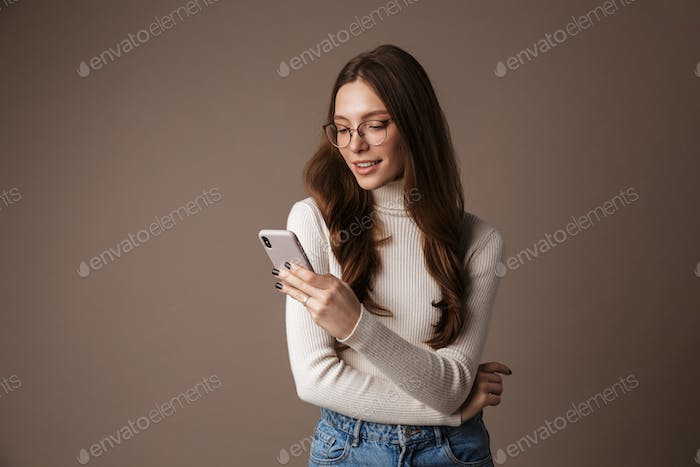 Photo of pleased beautiful woman using cellphone and smiling
