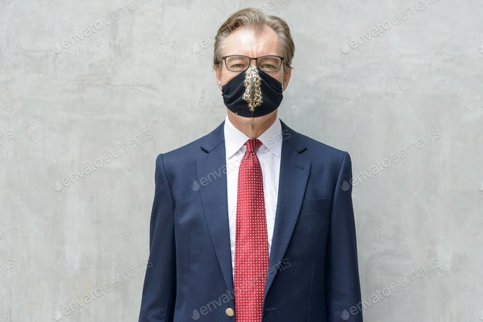 Mature businessman in suit with mask for protection from corona virus outbreak against concrete wall