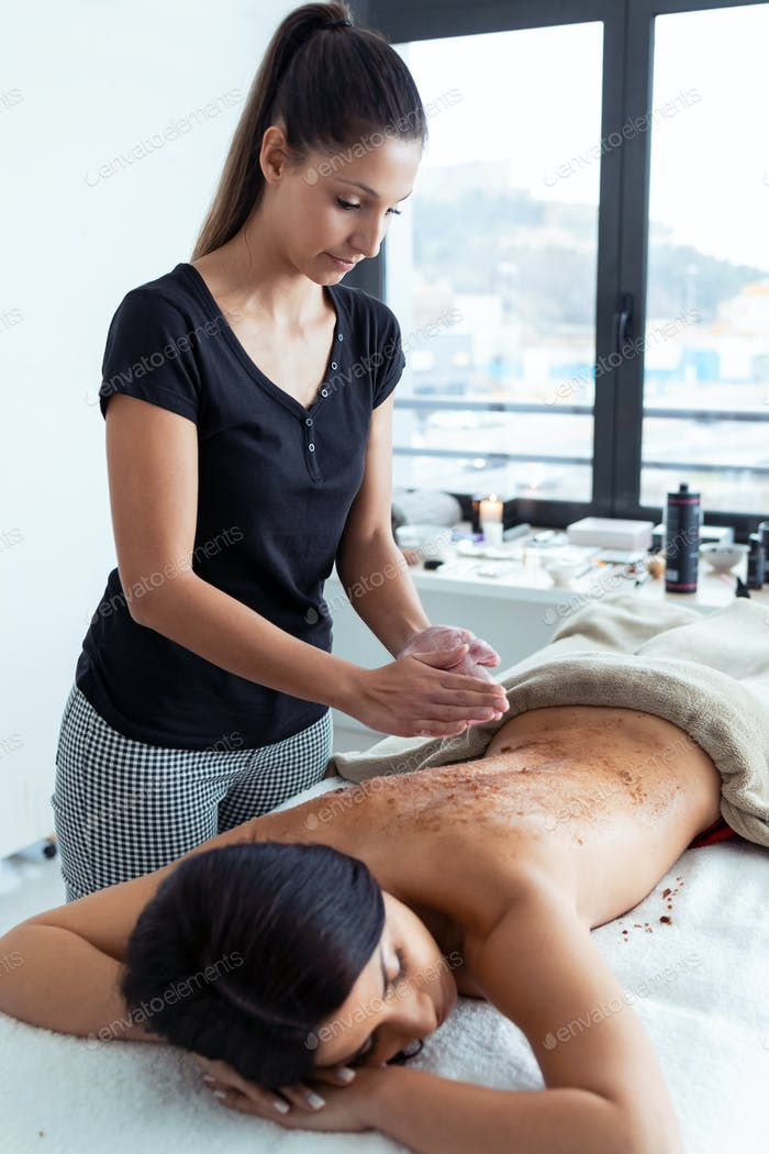 woman applying chocolate cream for body treatment to a pretty woman on the spa center.