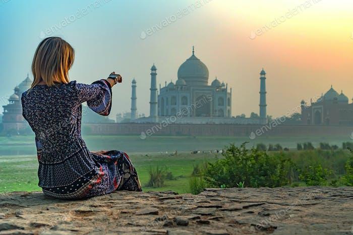 Beautiful girl points to Taj Mahal. Travel concept