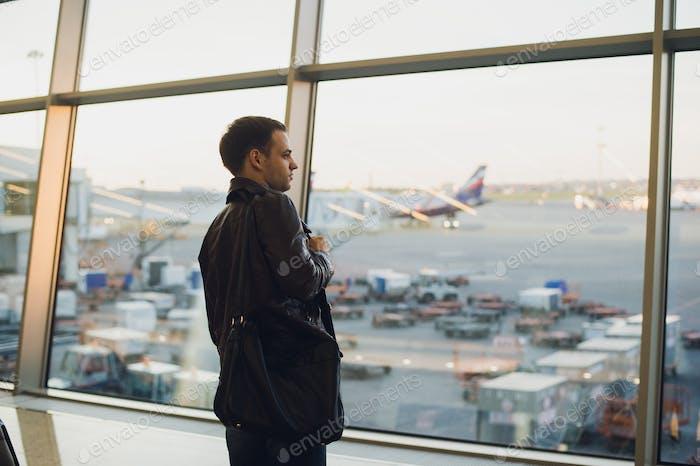 Reisekonzept mit einem jungen Mann im Flughafen-Interieur mit Blick auf die Stadt und einem Flugzeug vorbeifliegen.
