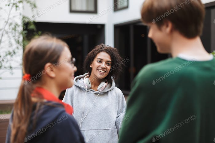 Joyful lady with dark curly hair in headphones standing and happily talking with her friends