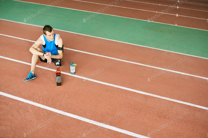 Handicapped Sportsman Resting on Running Track