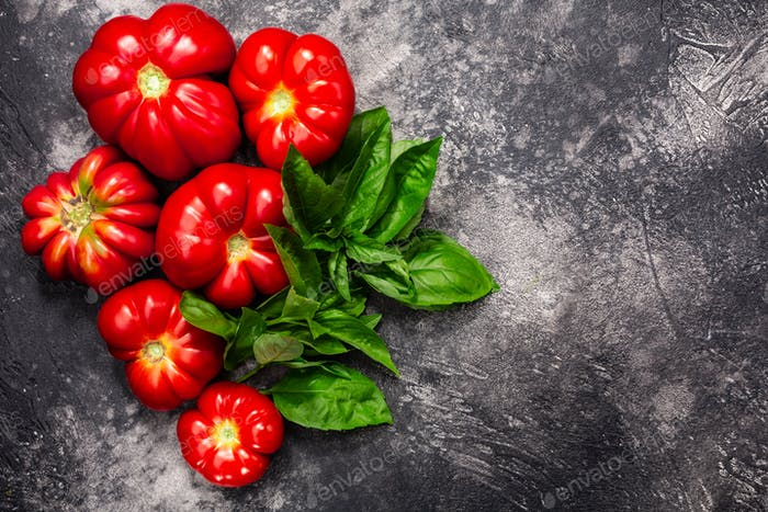 Heirloom ribbed  tomatoes and basil atop black textured backdrop, copy space, top view