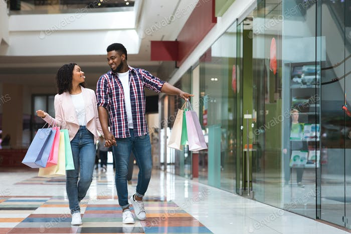 Black Friday Sales. Happy African Couple Walking With Shopping Bags In Mall