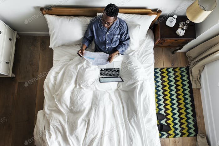 Business man in bed working