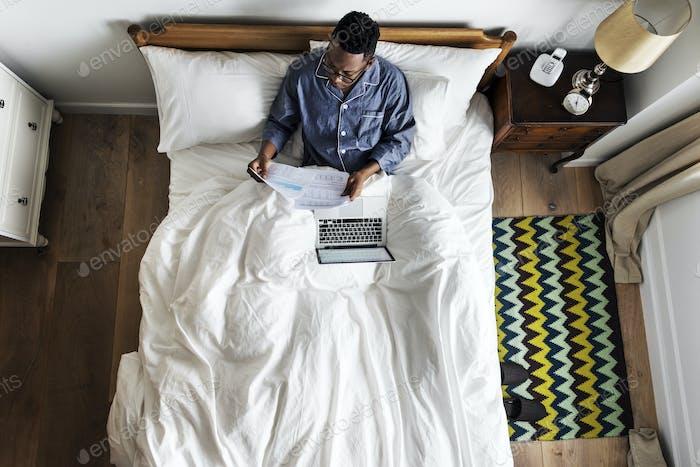 Geschäftsmann im Bett arbeiten