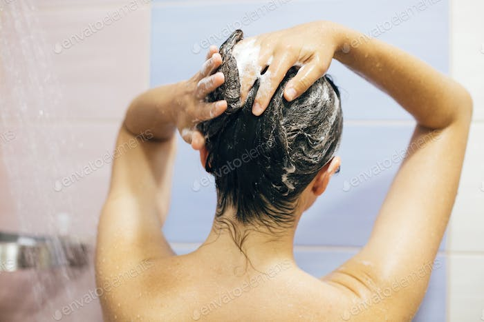 Young happy woman washing her hair with shampoo, foaming with hands