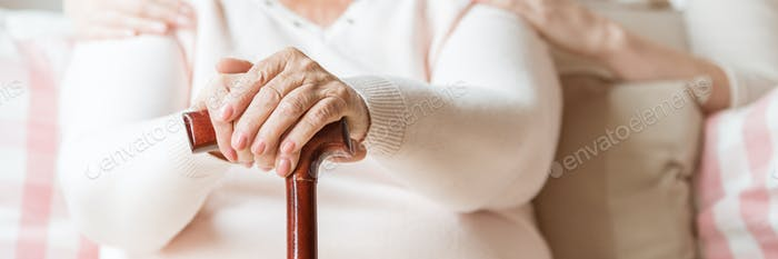 Close-up of an elderly woman's hands on a cane. Blurred backgrou