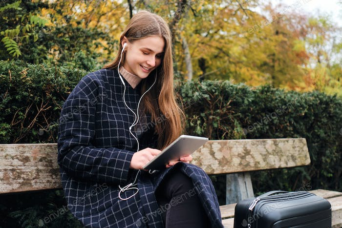 Pretty casual girl in earphones happily using tablet sitting with suitcase on bench in park