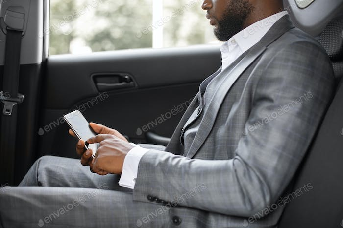Cropped of black businessman going by car to business meeting