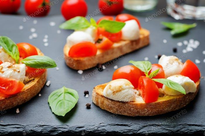 Caprese bruschetta with fresh tomatoes and Basil leaves