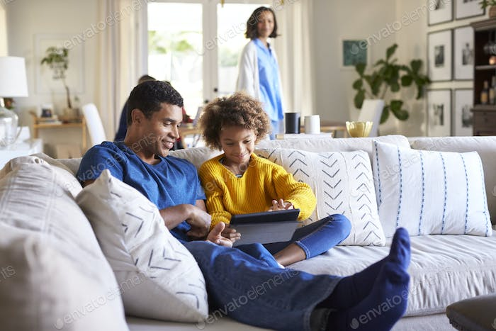 father sitting on sofa in the living room with his pre-teen daughter using tablet computer