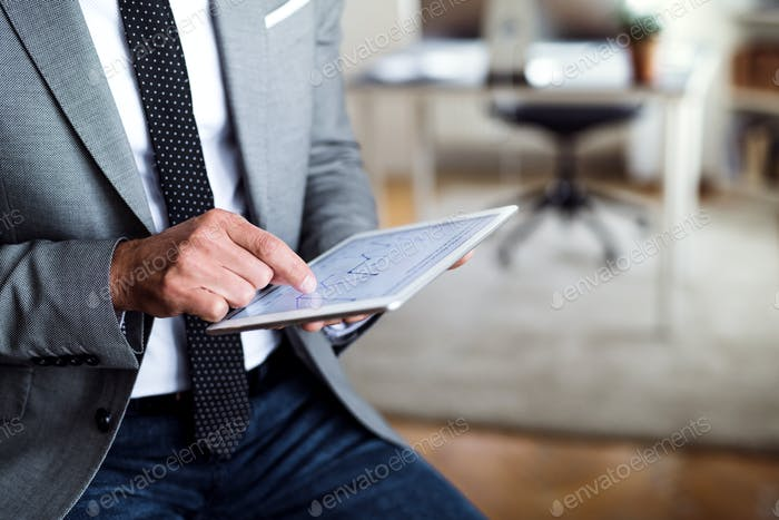 A midsection of businessman sitting in an office, using tablet. Copy space.