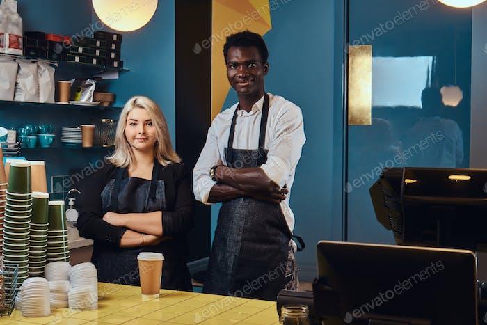 Zwei junge multirassische Baristas in Schürzen stehen in ihrem trendigen Coffeeshop herzlich willkommen.