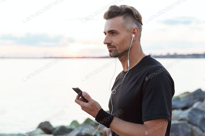 Portrait of a fit sportsman listening to music with earphones