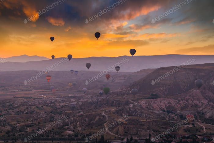 Hot air balloons flying over a volcanic landscape at Cappadocia, Turkey