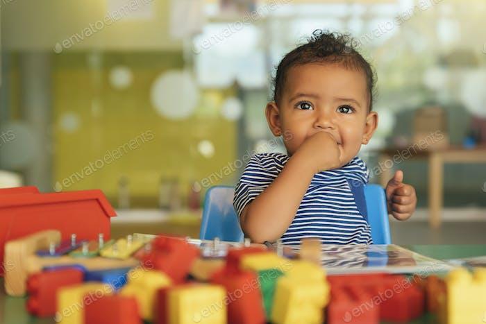 Glückliches Baby spielt mit Spielzeugblöcken.