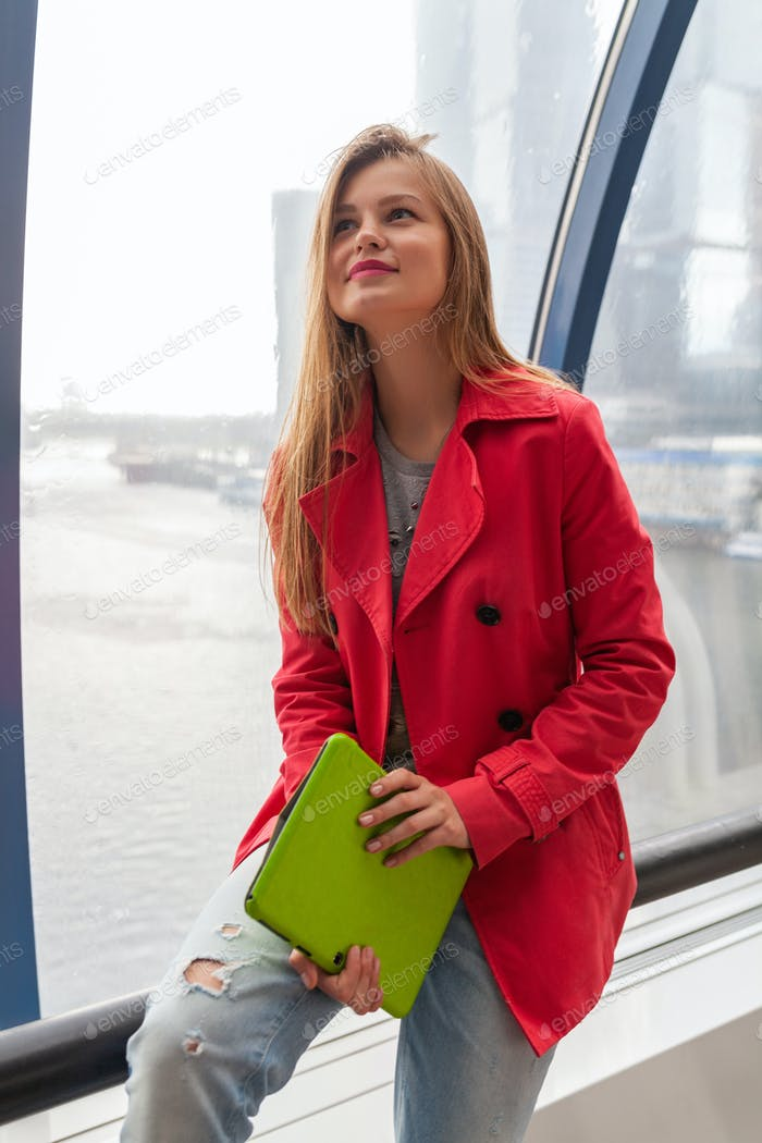 young pretty woman in casual outfit holding tablet laptop