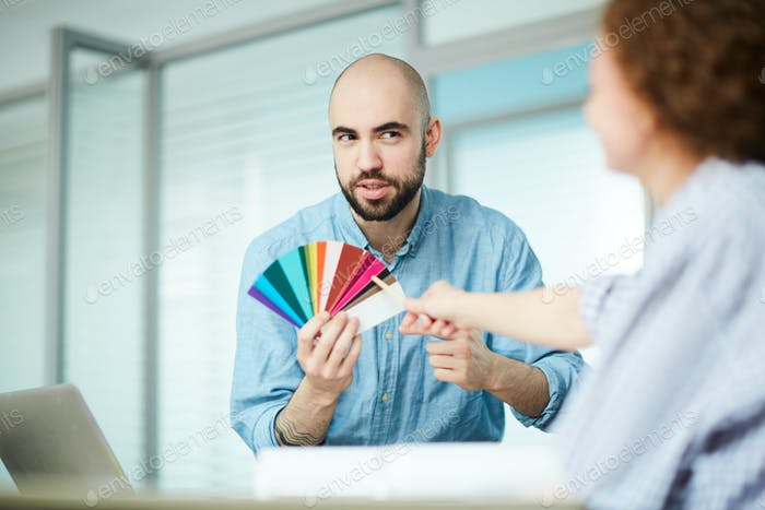 Bearded designer asking advice of colleague about color combination