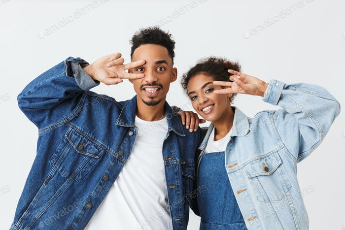 Playful african couple in denim shirts showing peace gestures