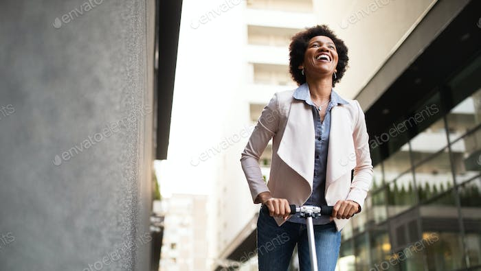 Happy woman on the electric scooter with background of office building