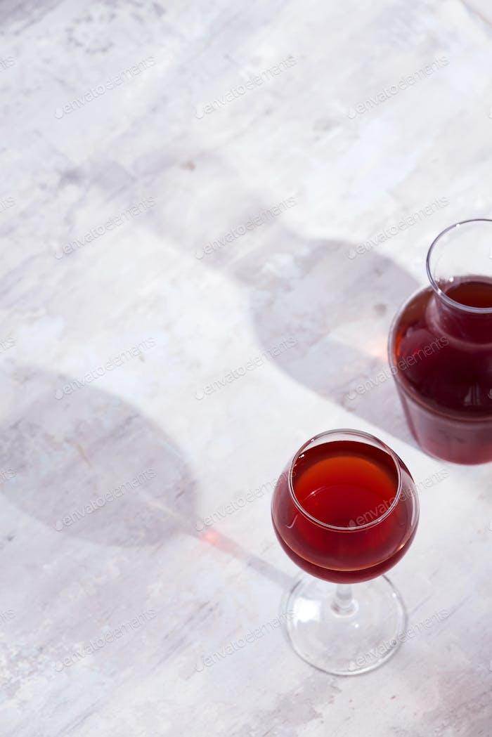 Rotwein in einem Weinglas mit Schatten auf Stein Hintergrund isoliert