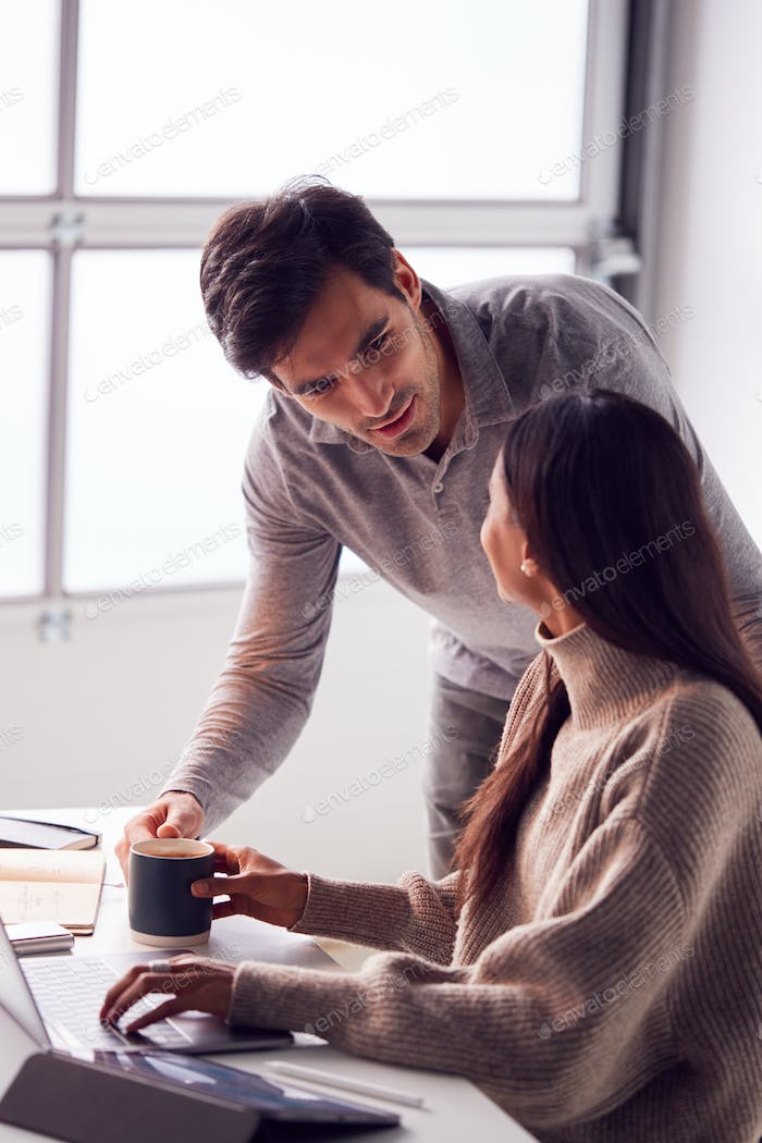 Businessman Bringing Female Colleague Working On Laptop At Desk A Cup Of Coffee