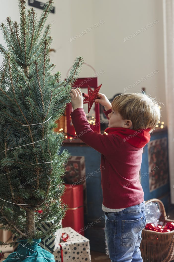 happy family with a young child decorating a christmas tree at home
