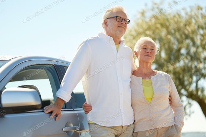 happy senior couple hugging at car in summer