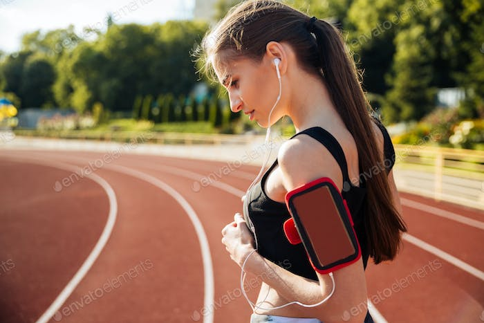 Side view of a female runner with mobile phone