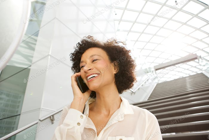 Close up attractive middle age african american woman smiling and talking with cellphone