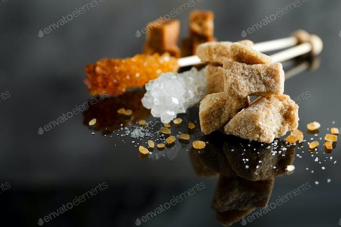 verschiedene Zuckerarten - brauner, weißer und raffinierter Zucker auf Schwarz