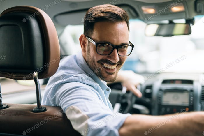 Portrait of a businessman driving car