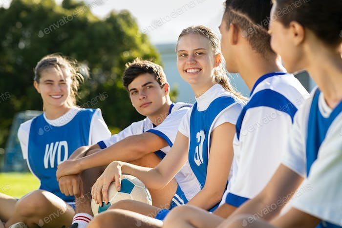 Happy smiling young football players sitting in field