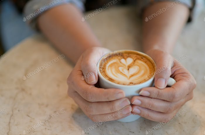 Cropped shot of Hand holding a heart pattern latte coffee cup.