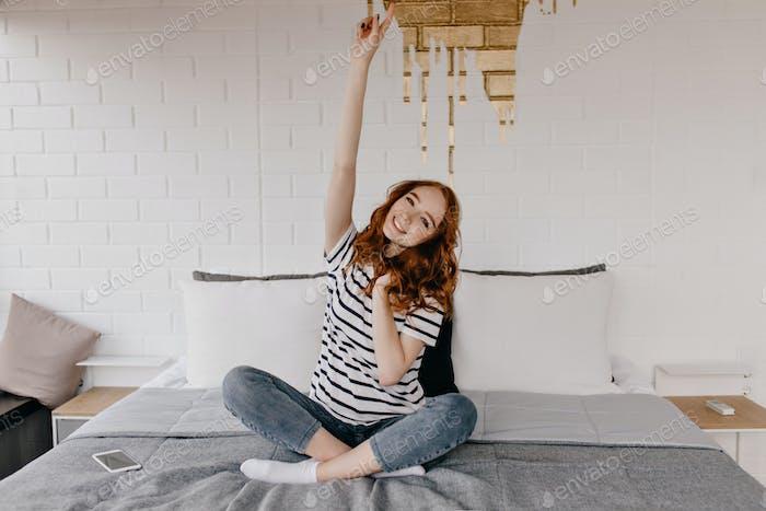 Chica bonita divertida en jeans posando en el dormitorio. Magnífica dama pelirroja sentada en la cama