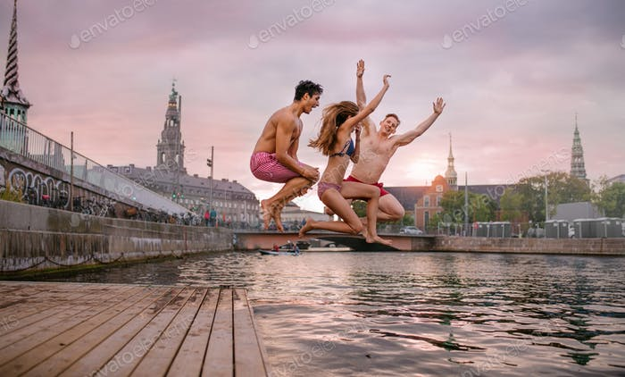 Young friends jumping from jetty into lake