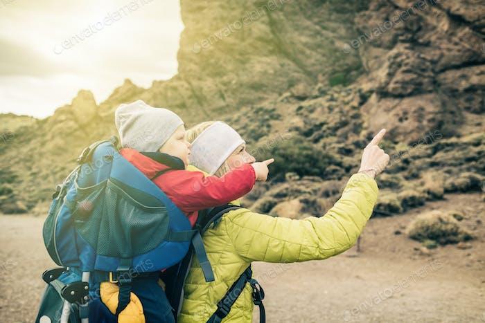 Super Mom mit Baby Jungen Wandern im Rucksack