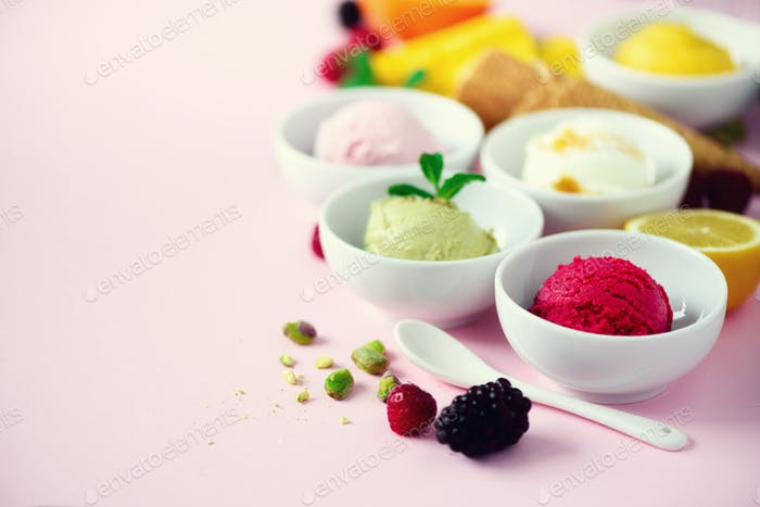Red, purple, yellow, green, white ice cream balls in bowls, waffle cones, berries, orange, mango