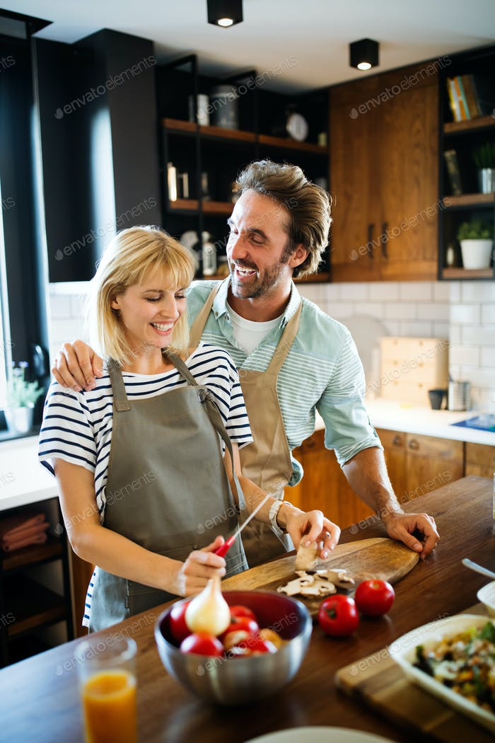 Happy couple cooking healthy food and having fun together in their kitchen