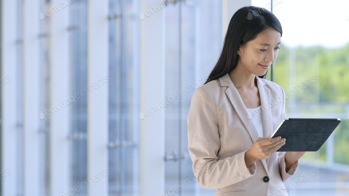 Professional Business woman looking at tablet computer in corporate building